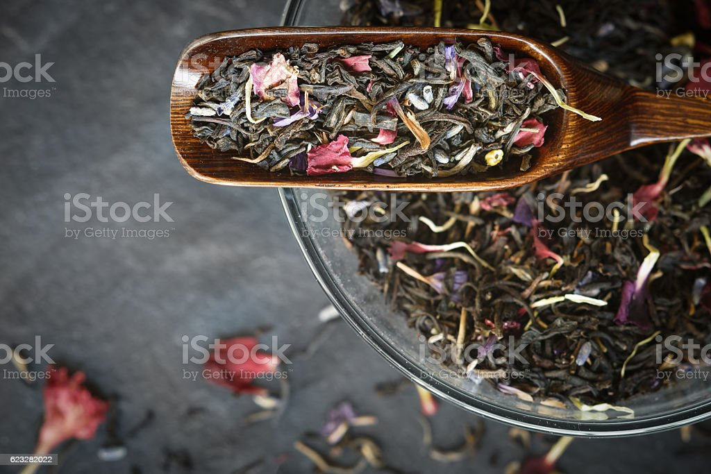 Black tea with flower  petals in wooden spoon top view Lizenzfreies stock-foto