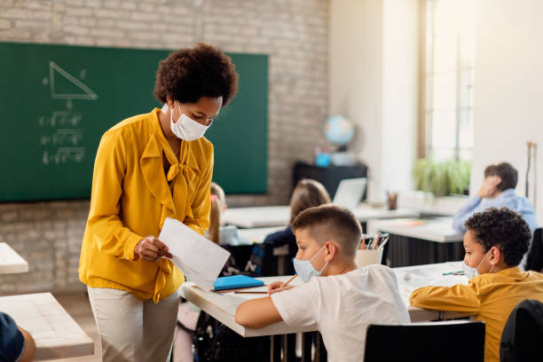 Black teacher and elementary student with face masks examining test result in the classroom. stock photo