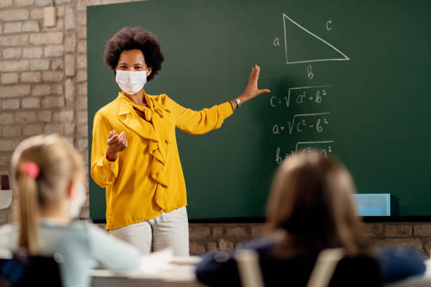Black teacher wearing face mask while explaining math lesson in the classroom. stock photo