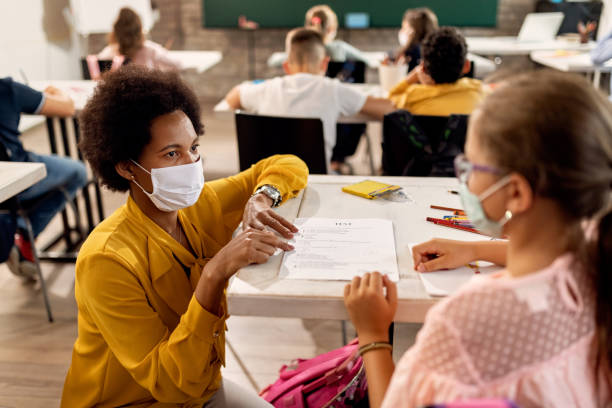 Black teacher with a face mask explaining exam results to elementary student in the classroom. African American teacher and schoolgirl wearing protective face masks while discussing about test results on a class at the school. classroom stock pictures, royalty-free photos & images