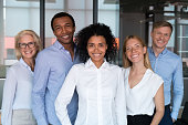 Attractive successful people standing together smiling posing looking at camera feels proud and satisfied. Multi-ethnic businesspeople led by afro mixed race woman photographing in modern office room