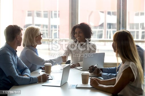 istock Black team leader shaking hands with aged businesswoman during meeting 1127397312