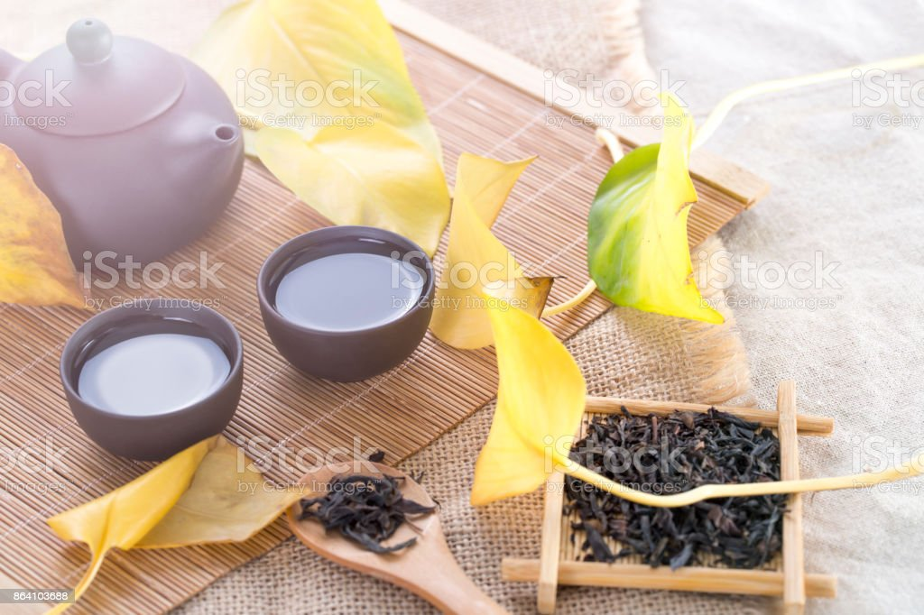 Black teapot and cups with yellow leaves on the table. Hot drinks. Autumn tea. royalty-free stock photo