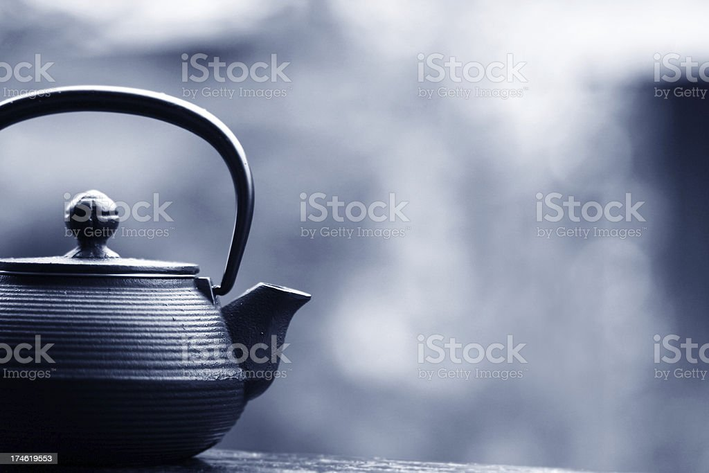 Black teapot in front of blurry background stock photo