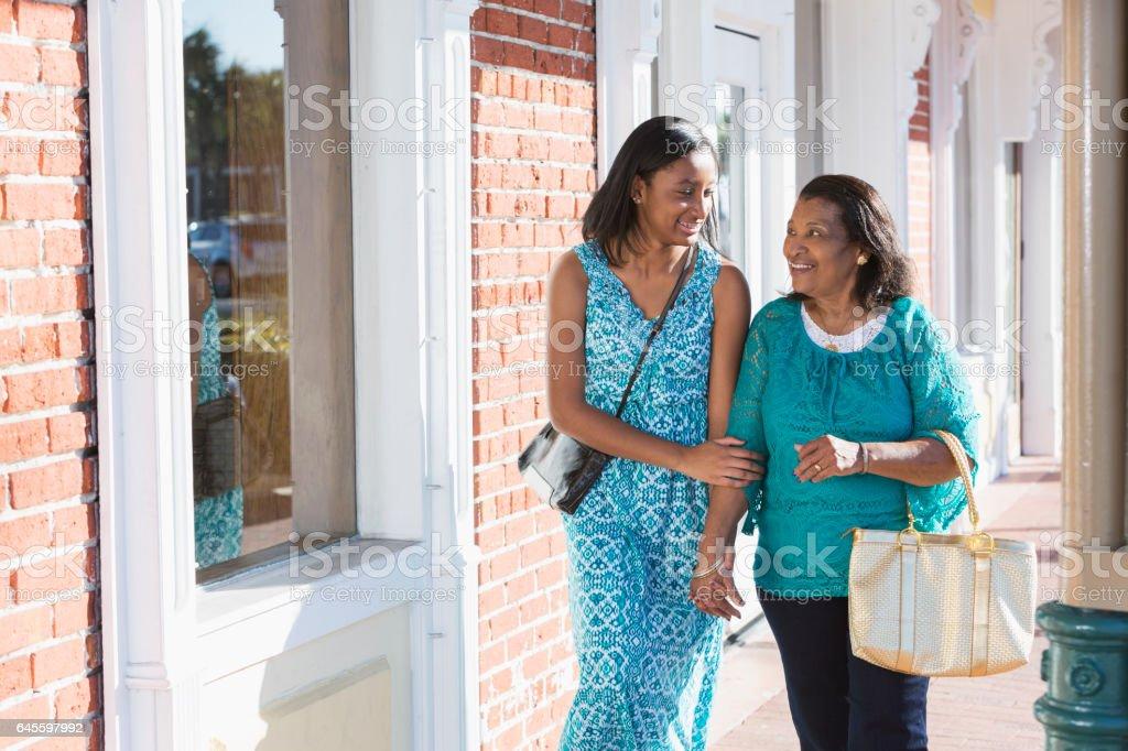 Black teenage girl walking with her grandmother stock photo