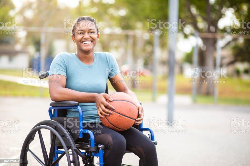 Negro adolescente con baloncesto en silla de ruedas - foto de stock