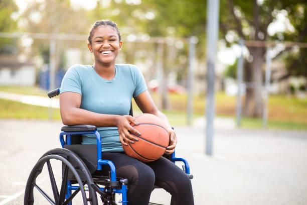adolescente noire avec le basket-ball en fauteuil roulant - sports en fauteuil roulant photos et images de collection