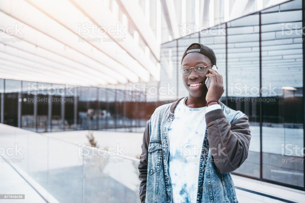 Black teenage studend talking on smartphone stock photo