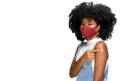 black teenager wearing protective mask against covid-19 with a smile on his face shows the vaccine brand, isolated on white background
