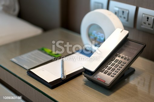 Black telephone and note in front and bed in the background, focus on the telephone,for room service,communication themes in hotel or resort.