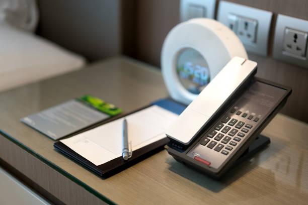 Schwarz Telefon und beachten Sie vor und Bett im Hintergrund, Schwerpunkt am Telefon, Zimmer-Service, Kommunikation Themen in Hotel oder Resort. – Foto