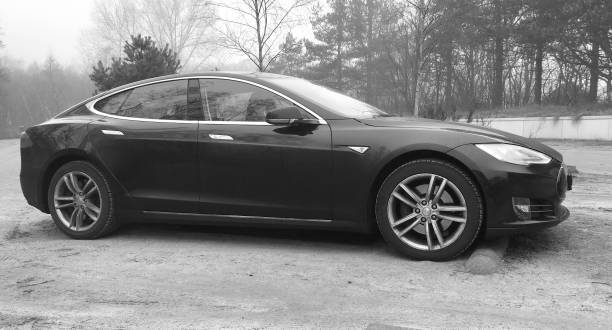 Black Tesla model S - black and white Schoorl, The Netherlands - February 18, 2017: Black Tesla model S parked in a public parking lot. Nobody in de vehicle. tesla model s stock pictures, royalty-free photos & images