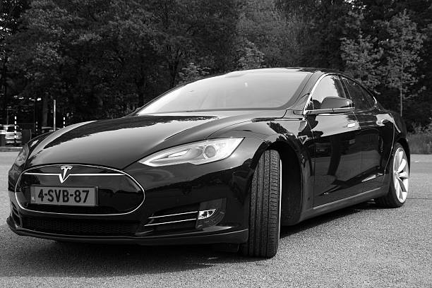 Black Tesla Motors Model S - Front view black white Arnhem, The Netherlands - May 17, 2015:  Black Electric Tesla Motors Model S parked on a parking lot (black white) . Tesla Motors is an American automotive and energy storage company that designs, manufactures, and sells electric cars, electric vehicle powertrain components and battery products. tesla model s stock pictures, royalty-free photos & images