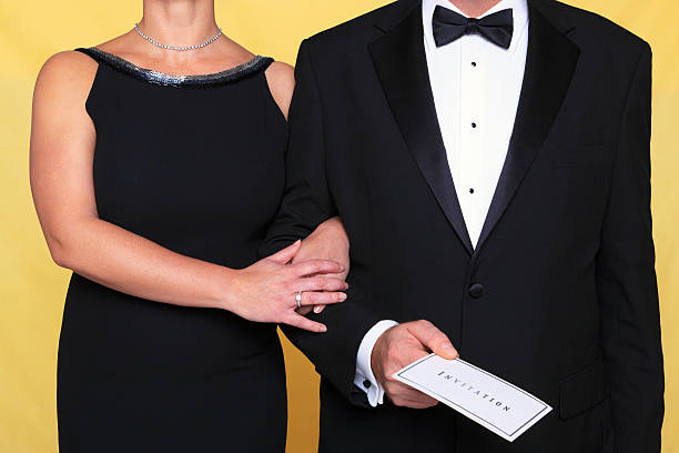 Black tie evening dress invitation Photo of a couple in black tie evening wear, the man is holding an invitation. evening wear stock pictures, royalty-free photos & images