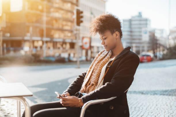 black tourist girl in street cafe with smartphone - esplanada portugal imagens e fotografias de stock