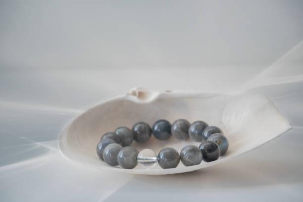 schwarzes turmalin-armband in einer muschel mit einem weichen, grauweißen hintergrund. - canda armband stock-fotos und bilder