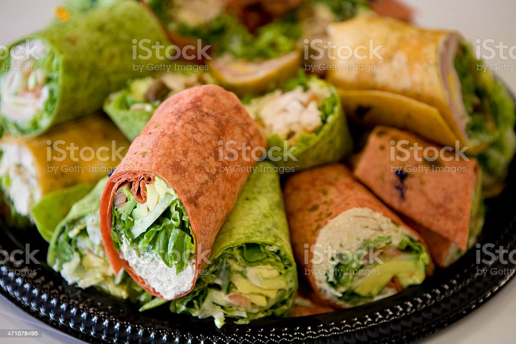 Black tray full of rolled sandwiches with colored tortillas stock photo
