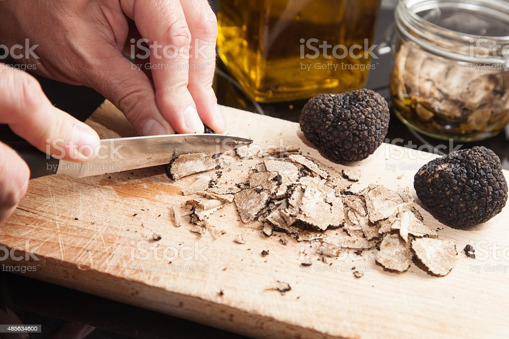Black truffle and knife on wooden background stock photo