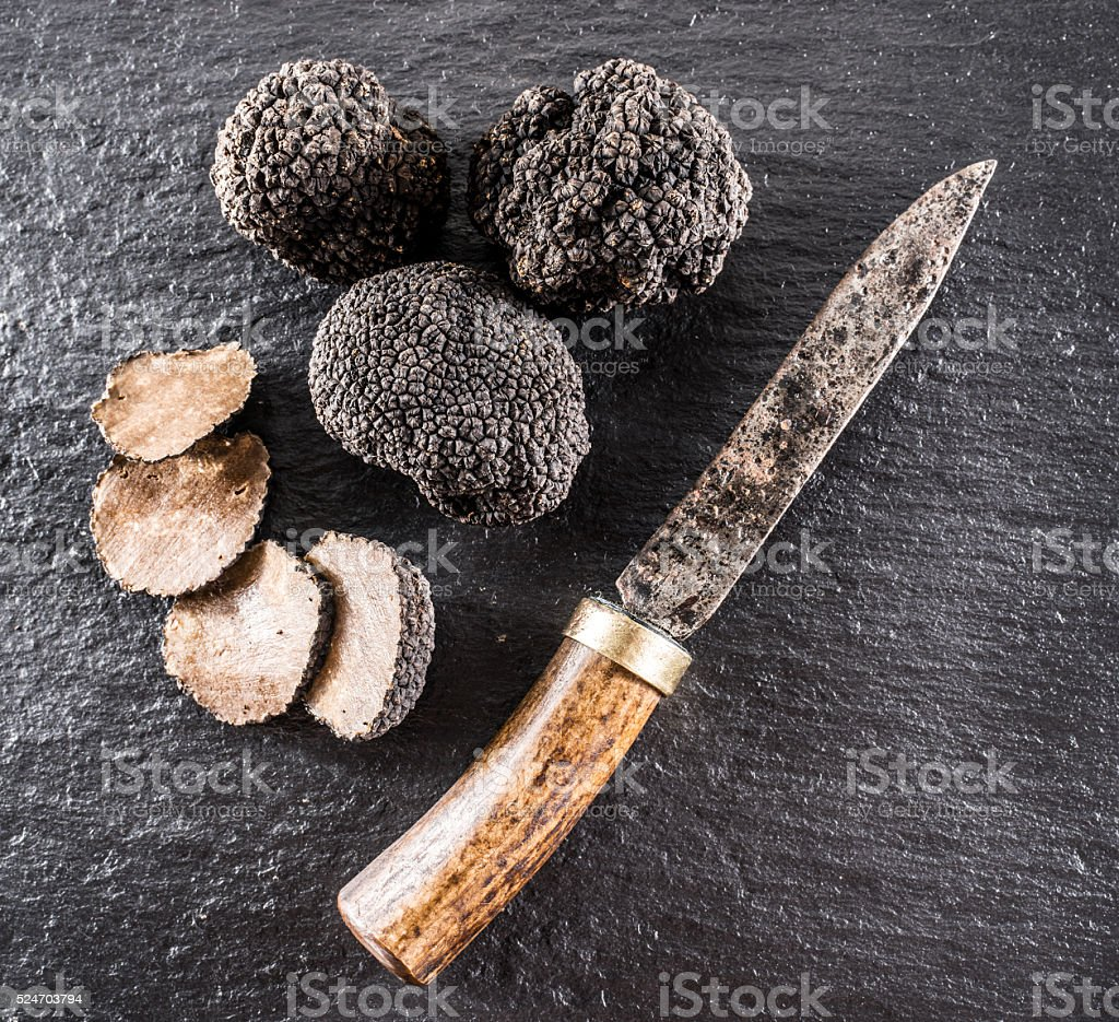 Black truffles and slices on the graphite board. stock photo