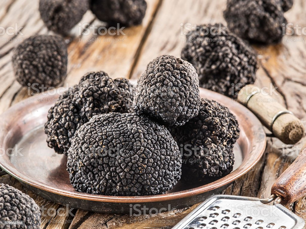 Black truffles on the plate on the old wooden table. stock photo