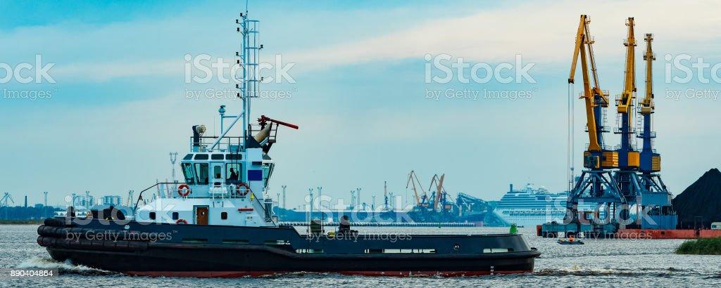 Black tug ship underway stock photo