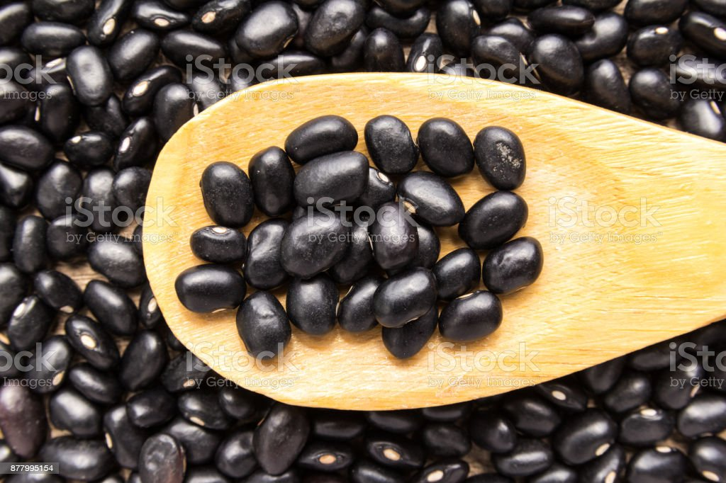 Black Turtle Bean legume. Grains in wooden spoon. Close up. stock photo