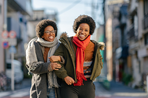 Black twin sisters are walking in the street arm in arm happily.