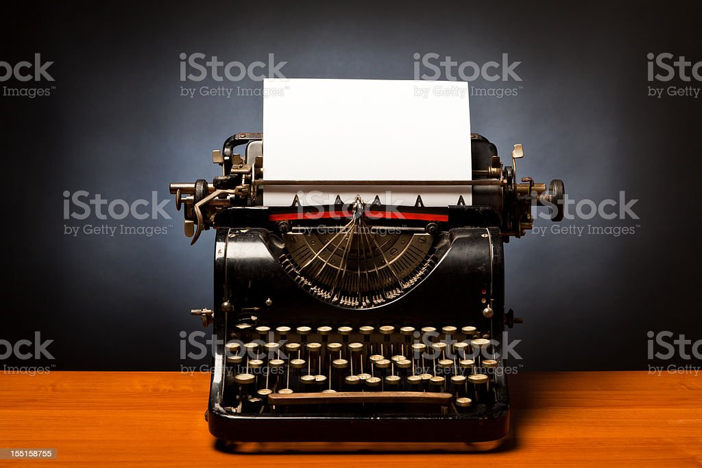 Black typewriter with blank white paper stuck royalty-free stock photo