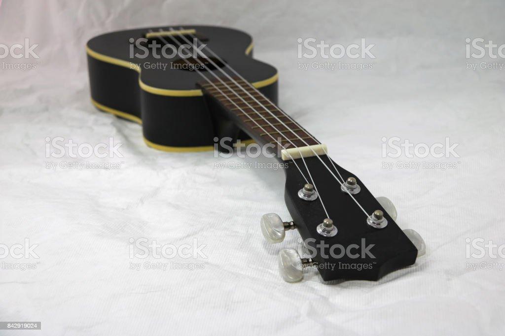Black ukulele on the white background. stock photo