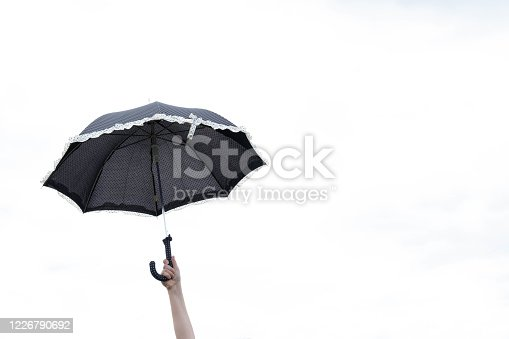 black umbrella in the hand of a little girl on a white sky, in the afternoon