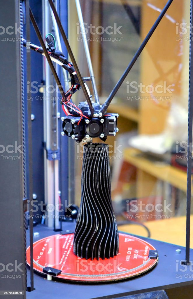 A black vase made on a 3d printer stands on the work surface stock photo