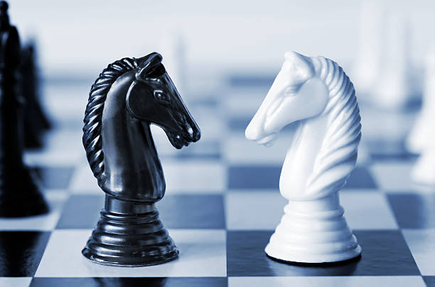 Black versus white chess knights on a board stock photo