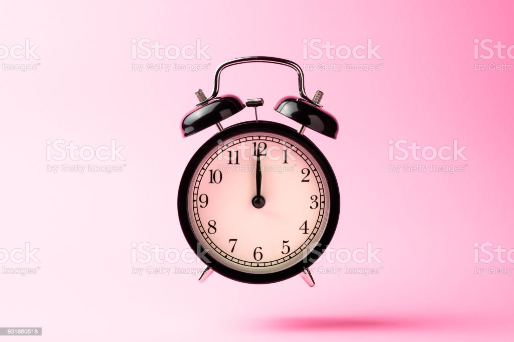 black vintage alarm clock floating on the air with pink color background stock photo