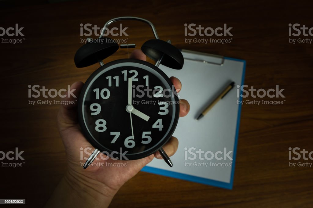 Black vintage alarm clock in hand with clipboard and blank white paper and pen, copy space for add your text, work on time or over time and deadline concept. - Royalty-free Accountancy Stock Photo