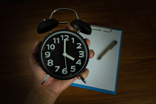 Black Vintage Alarm Clock In Hand With Clipboard And Blank White Paper And Pen Copy Space For Add Your Text Work On Time Or Over Time And Deadline Concept Stock Photo - Download Image Now