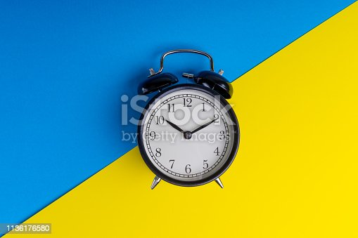 istock Black vintage alarm clock on a blue and yellow background 1136176580