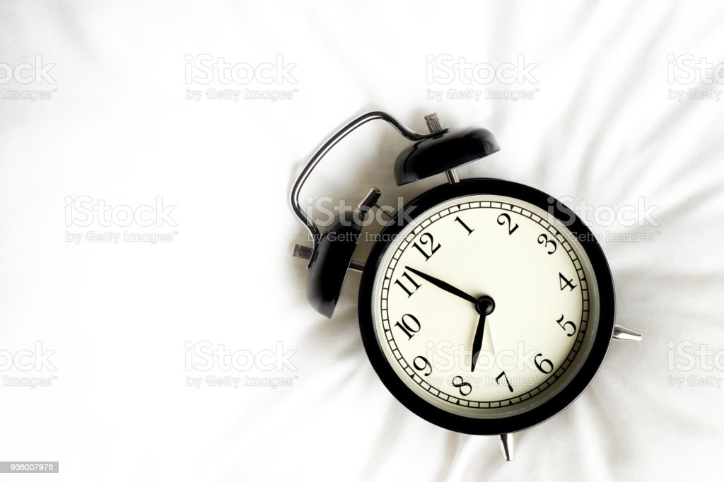 Black vintage alarm clock on white pillow or white bed stock photo