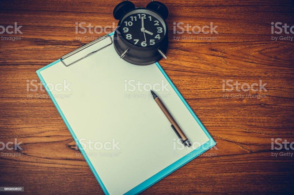 Zwarte vintage wekker met Klembord en blanco wit papier en pen, kopie ruimte voor uw tekst toevoegen, op tijd of over tijd en termijn concept werken. - Royalty-free Accountancy Stockfoto
