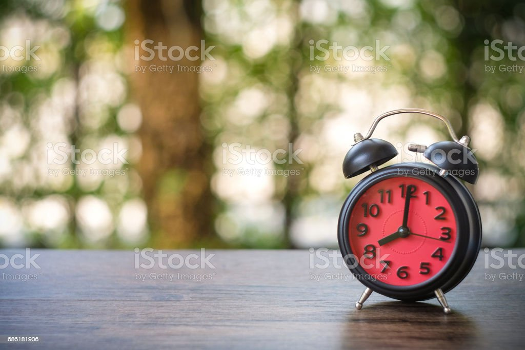 Black Vintage clock with red watch at eight o'clock on bokeh background stock photo