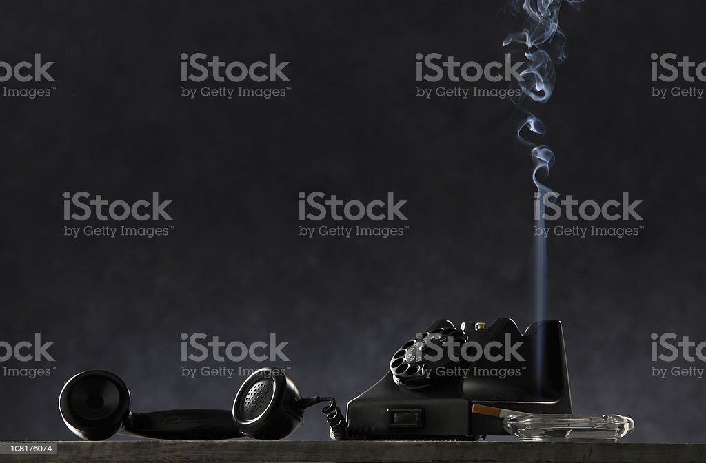 Black: Vintage Telephone and Cigarette in Ashtray on Table royalty-free stock photo