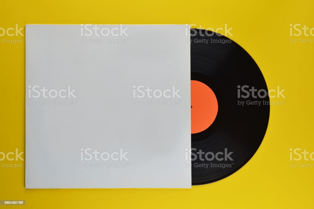 black vinyl record halfway out of white blank cover stock photo