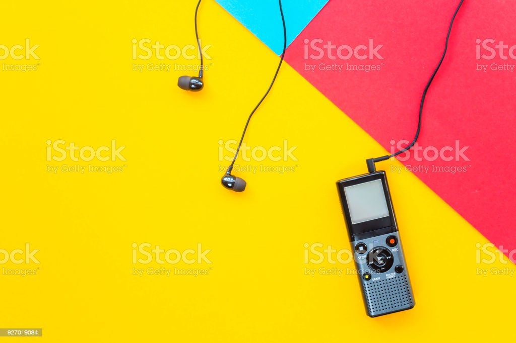 Black voice recorder with headphones on a combined yellow, blue and red background. Journalism concept. Equipment for work, interview and voice recording. Top view. Flat lay. Copyspace stock photo