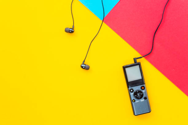 black voice recorder with headphones on a combined yellow, blue and red background. journalism concept. equipment for work, interview and voice recording. top view. flat lay. copyspace - dictaphone stock pictures, royalty-free photos & images