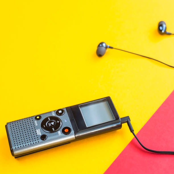 black voice recorder with headphones on a combined yellow, blue and red background. journalism concept. equipment for work, interview and voice recording. top view. flat lay. copyspace - recorder stock photos and pictures