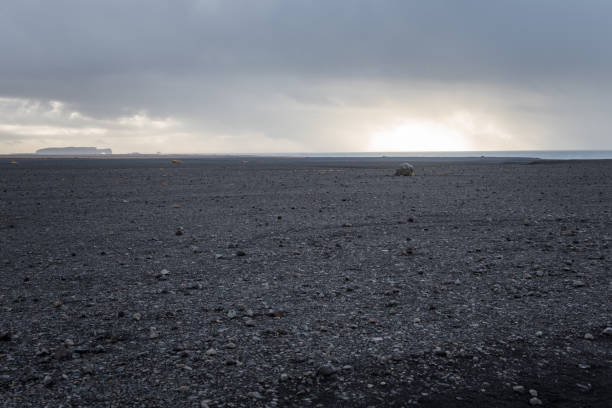 Black Volcanic Beach in Iceland in Autumn Deserted Black Beach in Iceland on a Cloudy Autumn Day. The Atlantic Ocean Is Visible on the Horizon. volcanic landscape stock pictures, royalty-free photos & images