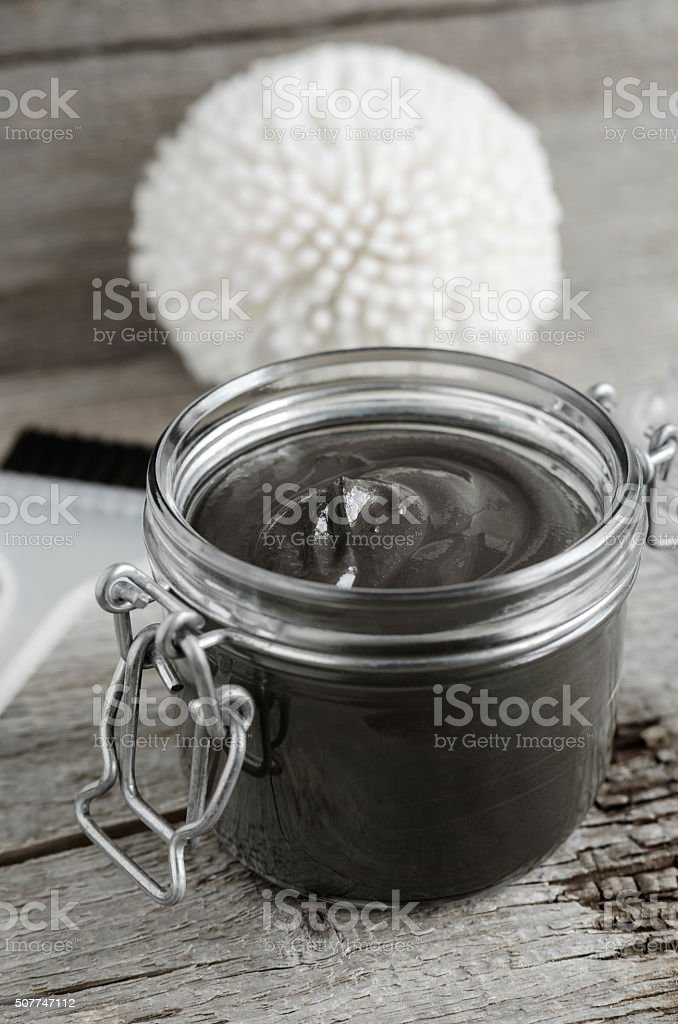 Black volcanic cosmetic clay in a glass jar stock photo