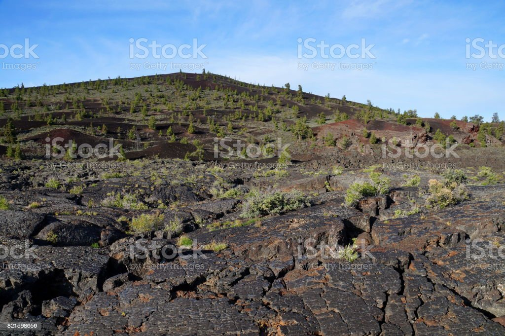 Black volcanic landscape: Cinder cone surrounded by pahoehoe and `a`a lava flows stock photo