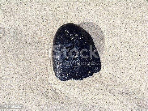 istock black volcanic stone on beach sand 1312480067