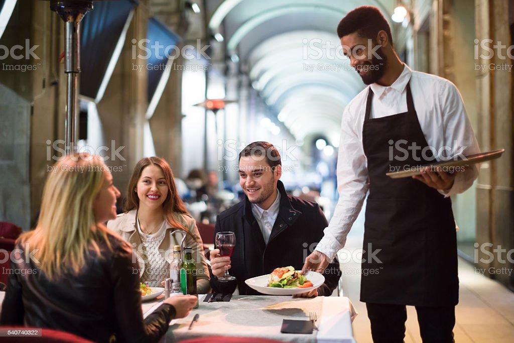 Black waiter serving table on the terrace stock photo