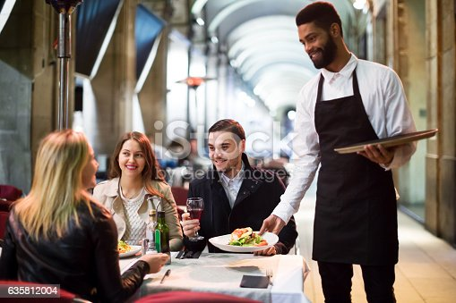 istock Black waiter serving table on the terrace 635812004